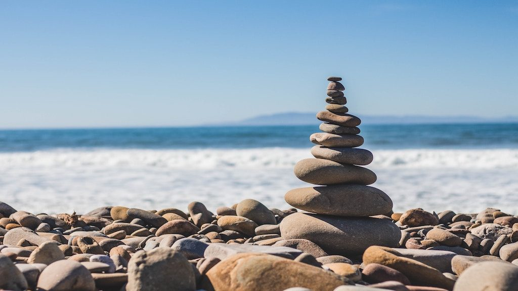 Six Building Blocks for Creating a Life of Balance and Wellness; image of rocks stacked near ocean